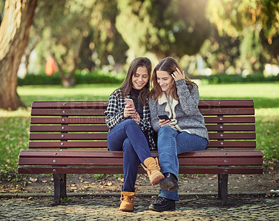 Buy stock photo Full length shot of two attractive young women using their cellphones while sitting in the park