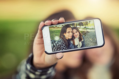 Buy stock photo Cropped shot of two attractive young women taking selfies while sitting in the park