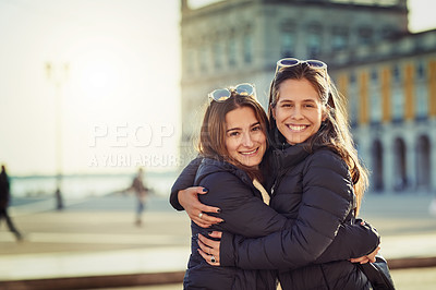 Buy stock photo Cropped portrait of two attractive young women spending a day in the city