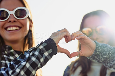 Buy stock photo Cropped portrait of two attractive young women making a heart shape with their hands while outdoors