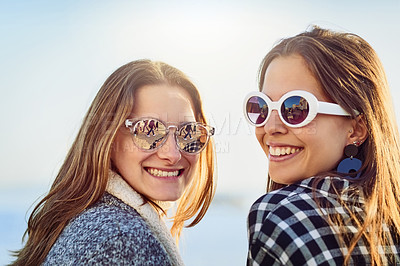 Buy stock photo Rearview portrait of two attractive young women spending a day by the ocean