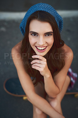 Buy stock photo Portrait of a cheerful young woman seated on a skateboard outside during the day