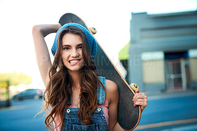 Buy stock photo Portrait of an attractive young female skater holding a skateboard behind her back outside during the day