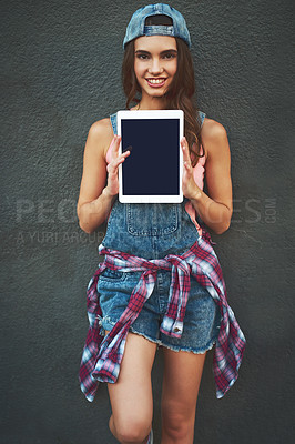 Buy stock photo Portrait of a cheerful young woman holding a digital tablet in front of her while standing against a grey background