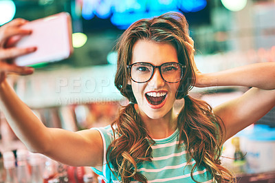 Buy stock photo Shot of a beautiful young woman taking a selfie in a diner