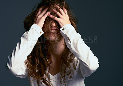 Buy stock photo Studio shot of an unrecognizable woman covering her face with her hair against a blue background