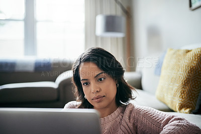 Buy stock photo Shot of an attractive young woman using a laptop at home