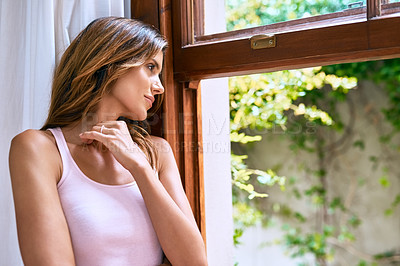 Buy stock photo Shot of an attractive young woman looking out the window at home