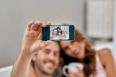 Buy stock photo Shot of a loving young couple taking selfies together at home