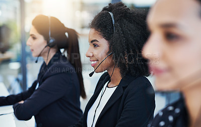 Buy stock photo Shot of a young woman working in a call center alongside her colleagues
