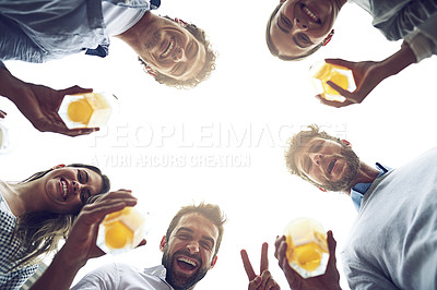 Buy stock photo Low angle portrait of a group of cheerful young work colleagues standing in a circle while drinking beer together outside during the day