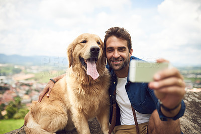 Buy stock photo Full length shot of a handsome young man and his dog taking selfies while resting during a hike in the mountains