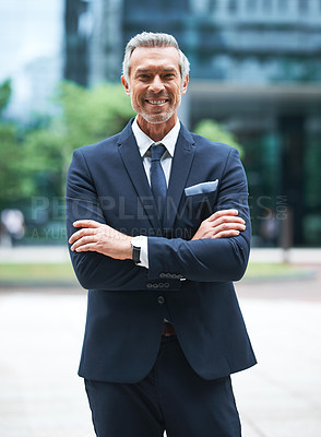 Buy stock photo Portrait of a handsome mature businessman in corporate attire standing with his arms folded outside during the day