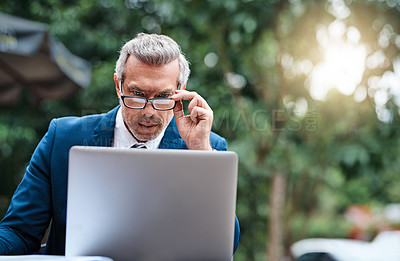 Buy stock photo Shot of a handsome mature business in corporate attire using a laptop outside during the day