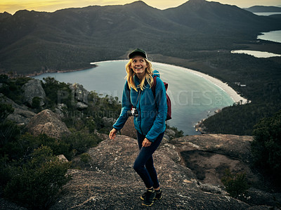 Buy stock photo Full length shot of an attractive young woman hiking through the mountains