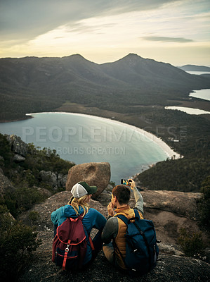 Buy stock photo Rearview shot of a young couple taking selfies while sitting on a mountain peak