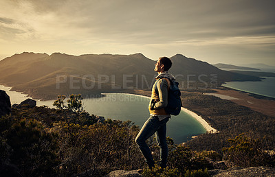 Buy stock photo Full length shot of a young man hiking through the mountains