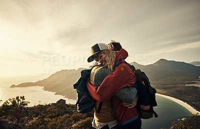 Buy stock photo Cropped shot of an affectionate young couple embracing while hiking through the mountains