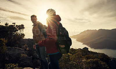 Buy stock photo Cropped shot of an affectionate young couple hiking through the mountains