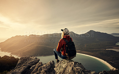 Buy stock photo Rearview shot of a young woman taking in the view while hiking through the mountains