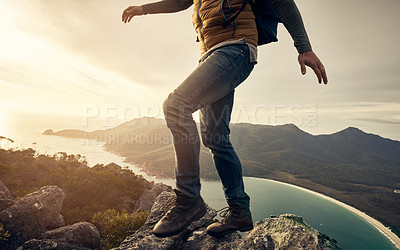 Buy stock photo Cropped shot of an unrecognizable young man hiking through the mountains