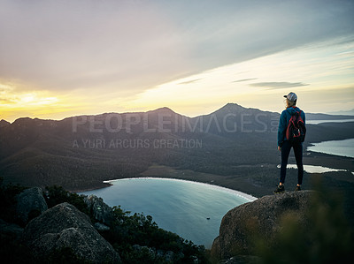 Buy stock photo Rearview shot of a young woman taking in the view while standing on a mountain peak
