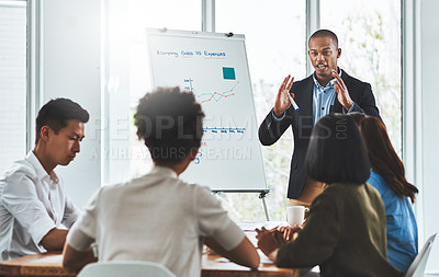 Buy stock photo Shot of a young businessman delivering a presentation to his team in a modern office