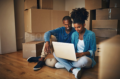 Buy stock photo Shot of a cheerful young couple browsing on a laptop together while being surrounded by cardboard boxes inside at home