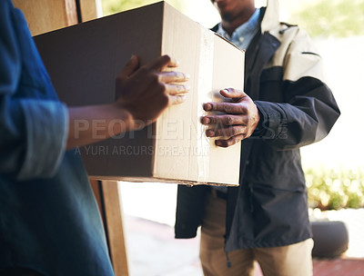 Buy stock photo Shot of an unrecognizable woman receiving a package from a deliveryman at home during the day