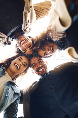 Buy stock photo Low angle portrait of a group of young friends huddled together while looking down at the camera outside during the day