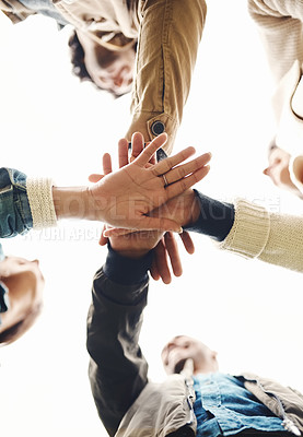 Buy stock photo Low angle shot of a group of young friends forming a huddle with their hands together outside during the day
