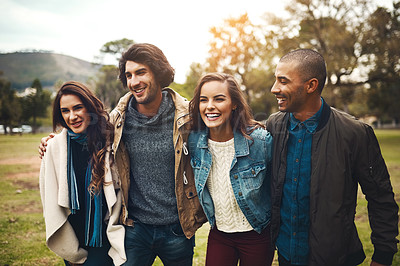 Buy stock photo Portrait of a group of cheerful young friends huddled together while walking in a park outside during the day