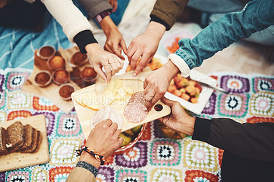 Buy stock photo Shot of a group of unrecognizable people's hands taking food from a plate at a picnic outside during the day