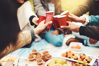 Buy stock photo Shot of a group of unrecognizable people celebrating with a celebratory toast at a picnic outside during the day