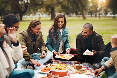 Buy stock photo Shot of a group of cheerful young friends having a picnic together outside in a park during the day