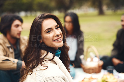 Buy stock photo Portrait of a cheerful young woman seated with his friends at a picnic outside during the day
