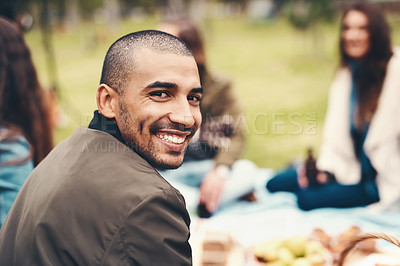 Buy stock photo Portrait of a cheerful young man seated with his friends at a picnic outside during the day