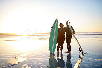 Buy stock photo Shot of a mature couple standing with their surfboards at the beach