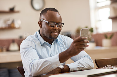 Buy stock photo Cropped shot of a handsome young businessman sending a text message while working at home
