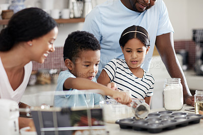 Buy stock photo Cropped shot of a young family baking together in the kitchen at home