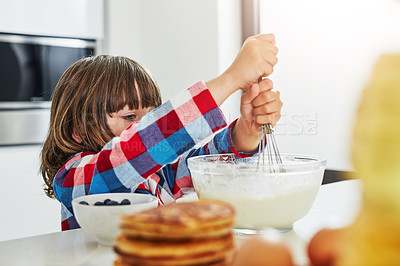 Buy stock photo Cropped shot of an adorable little boy making pancakes in the kitchen at home
