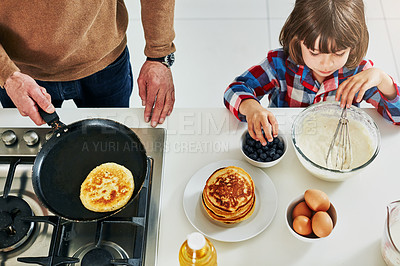Buy stock photo High angle shot of an adorable little boy making pancakes with his unrecognizable father in the kitchen at home