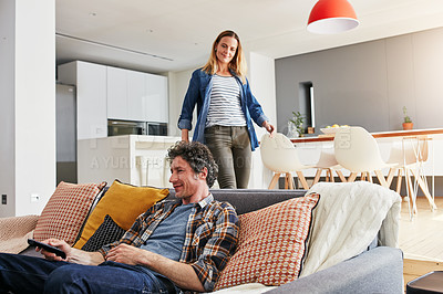 Buy stock photo Cropped shot of a mature man chilling on the sofa while his wife is coming to join him in the living room at home