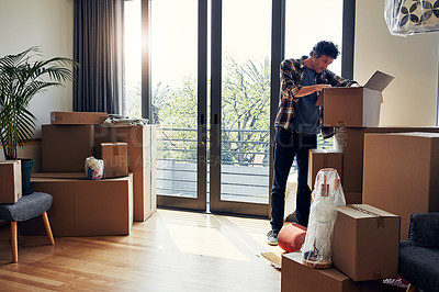 Buy stock photo Shot of a focused middle aged man packing out a box at his new home inside during the day