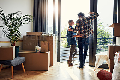 Buy stock photo Shot of a cheerful middle aged couple looking into each other's eyes while being surrounded by boxes on moving day inside at home during the day