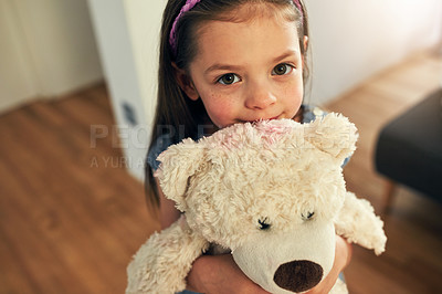 Buy stock photo High angle portrait of an adorable little girl tightly hugging her teddy at home during the day