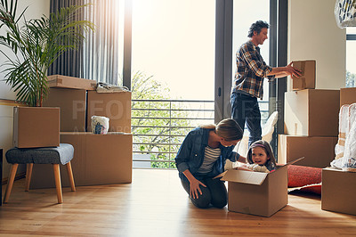 Buy stock photo Shot of a cheerful loving family packing out boxes together in their new home during the day