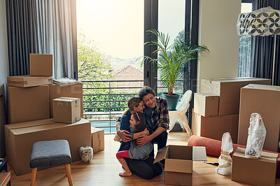Buy stock photo Shot of a cheerful loving family packing out boxes together in their new home while giving each other a big hug during the day