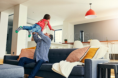 Buy stock photo Shot of a cheerful middle aged father holding his young daughter in the air while playing and being seated on the couch at home during the day