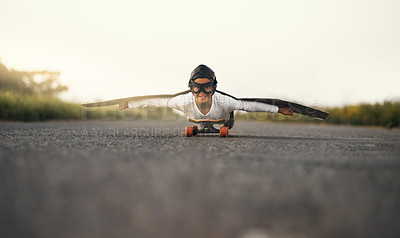 Buy stock photo Portrait of a young boy pretending to fly with a pair of cardboard wings while riding a skateboard outside
